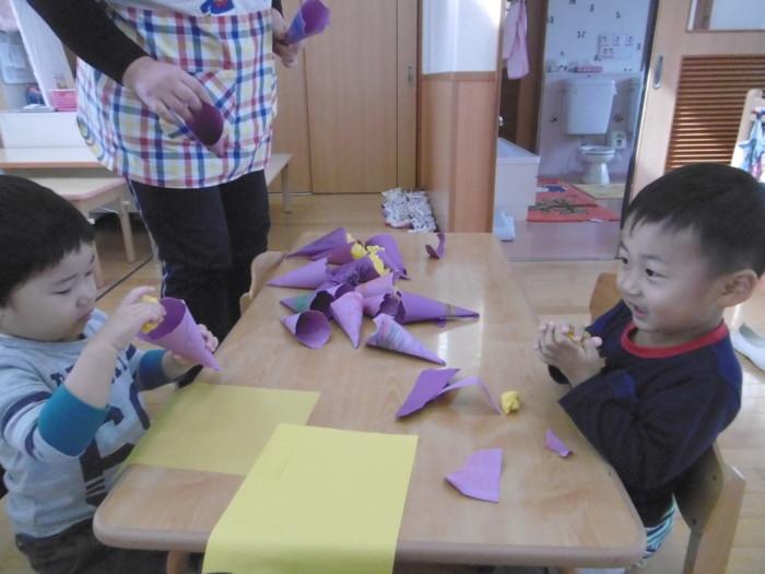 """紫の画用紙で作った""""皮""""の中へギュッギュッと入れました。"""